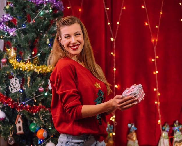 Lächelnde frau mit weihnachtsgeschenk. feiertagswand