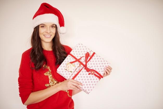 Lächelnde frau mit weihnachtsgeschenk