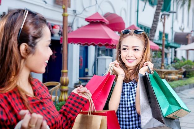 Lächelnde frau mit zwei asiaten mit vielen einkaufstaschen