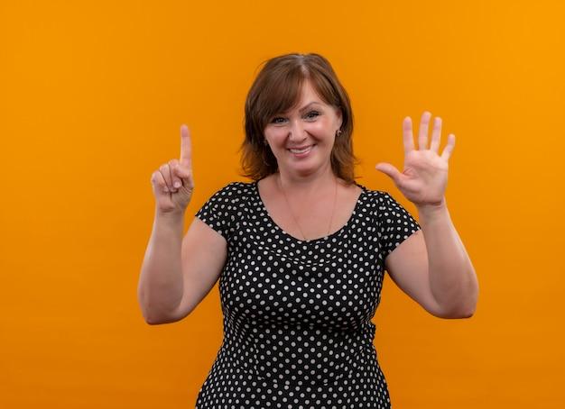 Lächelnde frau mittleren alters, die eins und fünf auf isolierter orange wand zeigt