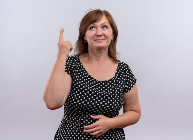 Lächelnde frau mittleren alters, die finger nach oben zeigt und hand auf bauch auf isolierte weiße wand legt