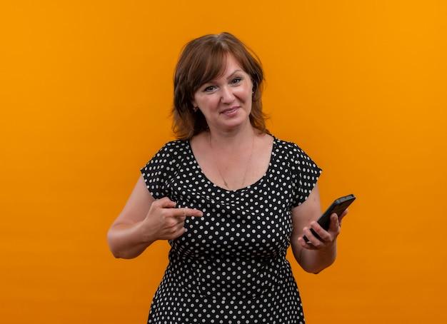 Lächelnde frau mittleren alters, die handy hält und mit dem finger darauf auf isolierte orange wand mit kopienraum zeigt