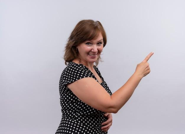 Lächelnde frau mittleren alters, die mit dem finger auf der rechten seite auf isolierte weiße wand zeigt