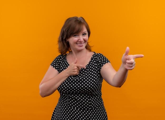 Lächelnde frau mittleren alters, die mit den fingern auf der rechten seite auf isolierte orange wand zeigt