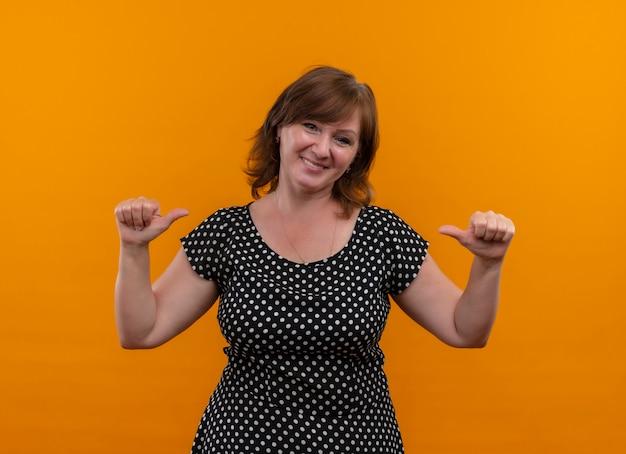 Lächelnde frau mittleren alters, die mit den fingern auf sich selbst auf isolierte orange wand zeigt