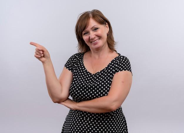 Lächelnde frau mittleren alters, die mit finger auf der linken seite auf isolierte weiße wand zeigt