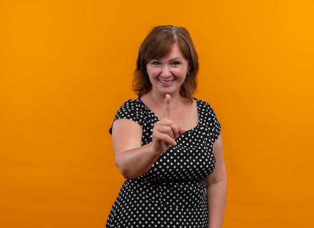 Lächelnde frau mittleren alters, die mit finger auf isolierte orange wand mit kopienraum zeigt