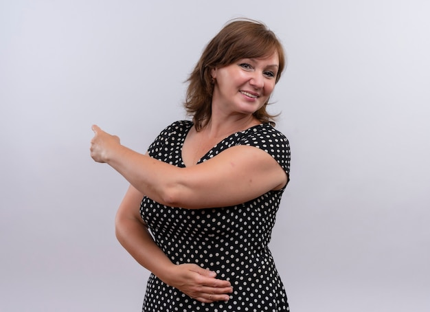 Lächelnde frau mittleren alters, die mit finger nach hinten zeigt und hand auf bauch auf isolierte weiße wand legt