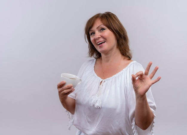 Lächelnde frau mittleren alters, die ok zeichen tut und tasse tee auf isolierter weißer wand hält