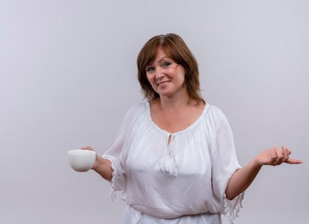 Lächelnde frau mittleren alters, die tasse tee hält und hand zur seite auf isolierte weiße wand legt