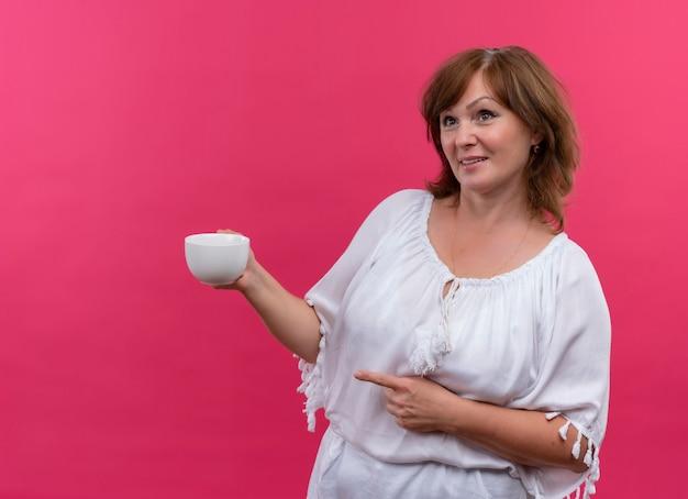 Lächelnde frau mittleren alters, die tasse tee hält und mit dem finger auf der linken seite auf isolierte rosa wand zeigt