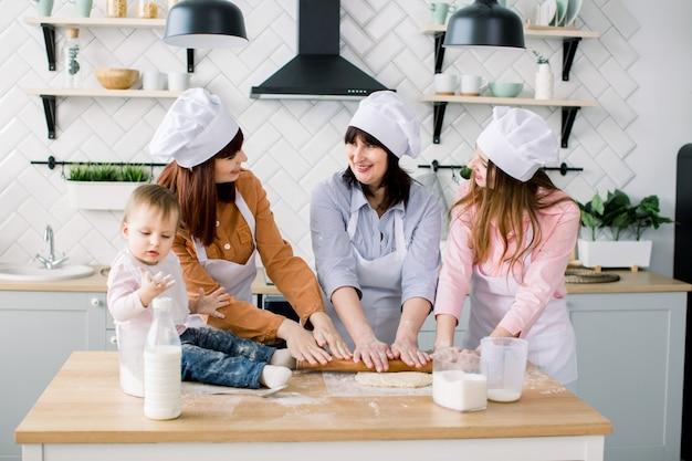 Lächelnde frau mittleren alters in der küchenschürze, die teig ausrollt und zwei töchter, die ihr helfen. kleines baby, das auf dem tisch sitzt und spaß hat. glückliche frauen in weißen schürzen, die zusammen backen