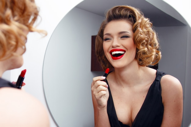 Lächelnde frau, model mit charmanter frisur und abendlichem make-up, roter lippenstift auf sinnliche lippen auftragen.
