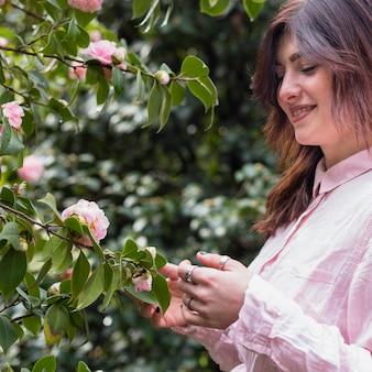 Lächelnde frau nahe den rosa blumen, die auf grünen zweigen wachsen