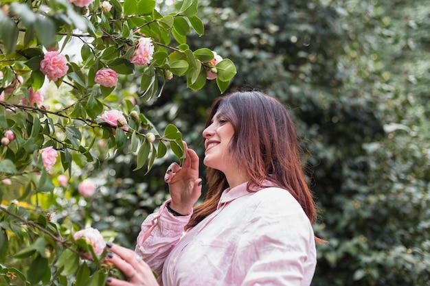 Lächelnde frau nahe vielen rosa blumen, die auf grünen zweigen wachsen