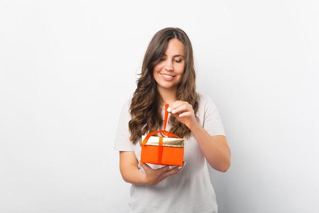 Lächelnde frau packt ihr geschenk aus und hebt das band an.