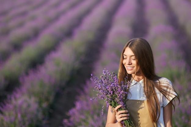 Lächelnde frau posiert mit blumenstrauß im lavendelfeld