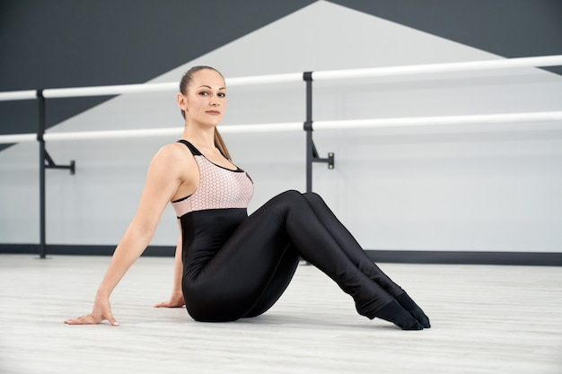Lächelnde frau sitzt auf dem boden im tanzstudio floor