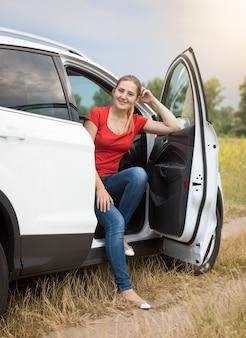 Lächelnde frau sitzt im auto auf dem feld
