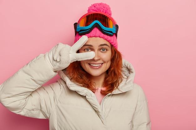 Lächelnde frau, trägt wintermütze und jacke, weiße handschuhe, macht friedensgeste über auge, hat saisonale ruhe, isoliert auf rosa wand.