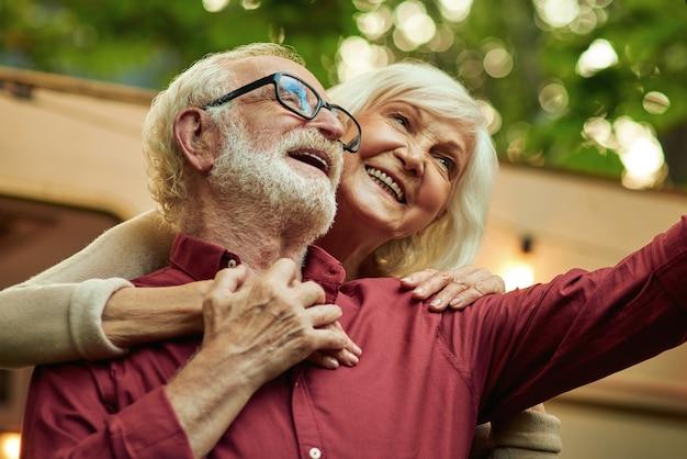 Lächelnde frau umarmt ihren ehepartner und macht ein foto