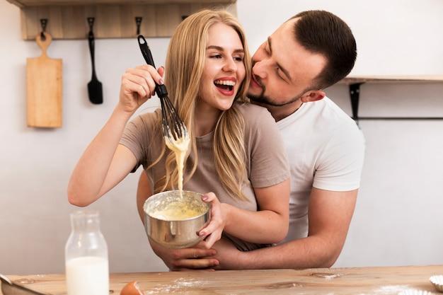 Lächelnde frau und mann, die zusammen kochen
