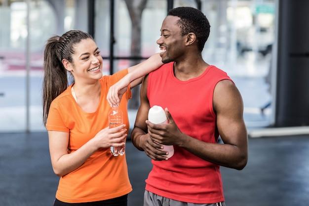 Lächelnde frau und mann nach anstrengung an der turnhalle