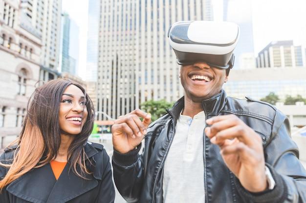 Lächelnde frau und mann, während er kopfhörer der virtuellen realität versucht