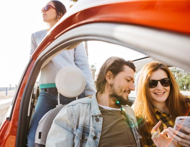 Lächelnde frau und positiver mann, die smartphone im auto nahe der dame sich lehnt, die sich vom auto lehnt
