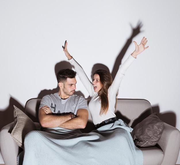 Lächelnde frau und verärgerter mann, die auf sofa fernsehen