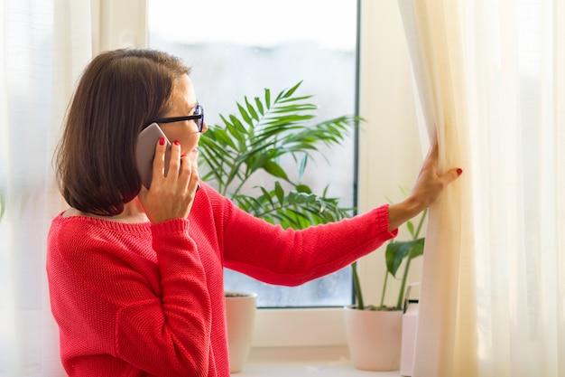 Lächelnde frau von mittlerem alter spricht am telefon