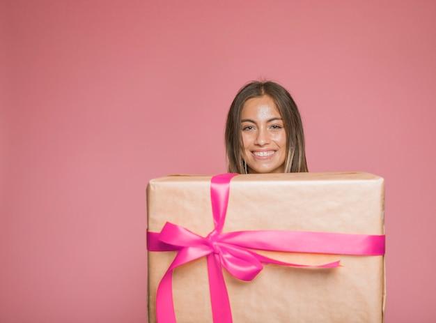 Lächelnde frau, welche die große geschenkbox eingewickelt mit rosa bogen gegen farbigen hintergrund hält