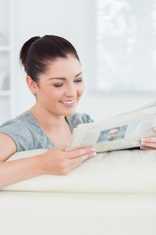 Lächelnde frau, welche die nachrichten beim sitzen auf einer couch liest