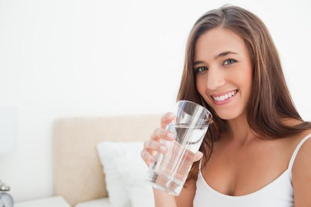 Lächelnde frau, wie sie ein glas wasser hält,