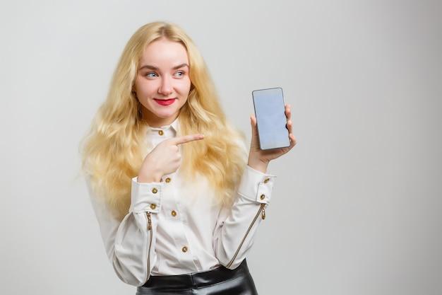 Lächelnde frau zeigt auf den smartphone, der auf weißem hintergrund steht