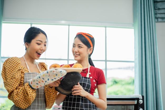 Lächelnde frau zeigt einige croissants, die sie erfolgreich gemacht hat.