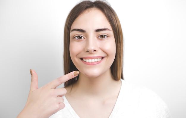 Lächelnde frau zeigt mit dem finger auf gesunde weiße zähne. zahnmedizin-konzept.