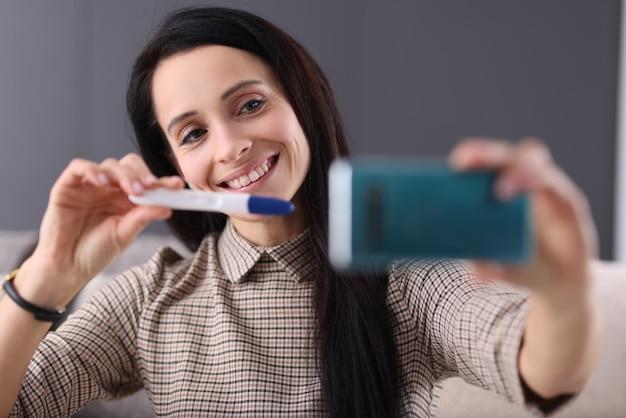 Lächelnde frau zeigt schwangerschaftstest im smartphone. so informieren sie ihren partner über das schwangerschaftskonzept