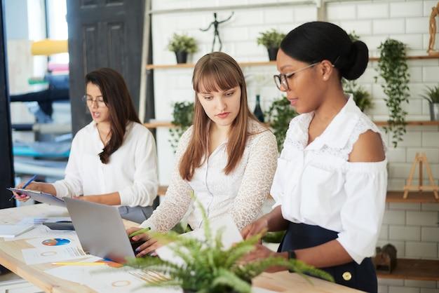 Lächelnde frauen arbeiten in einem modernen büro zusammen. feminismus. professionelle lächelnde geschäftsfrauen, die im büro stehen und geschäftspapiere besprechen.