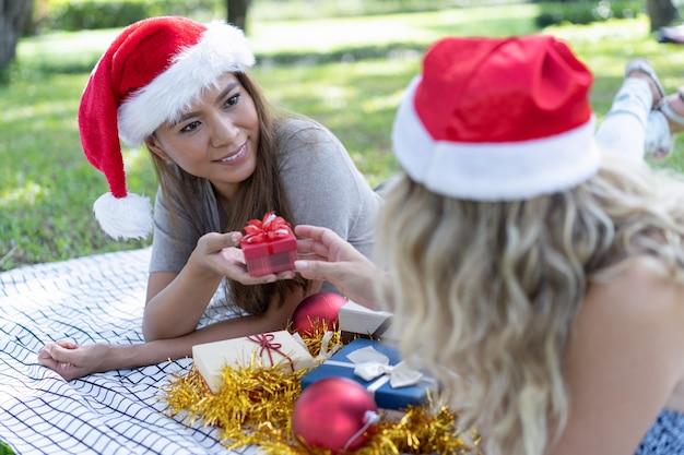 Lächelnde frauen, die auf decke mit weihnachtsgeschenken liegen
