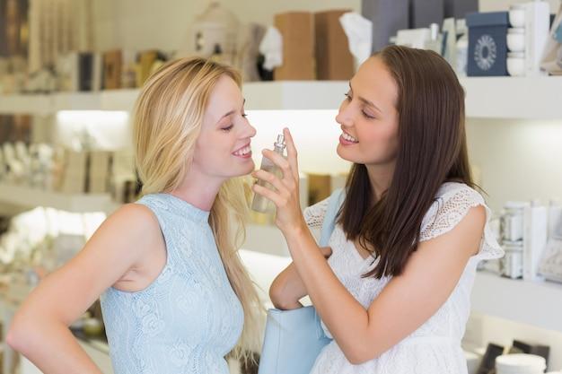 Lächelnde frauen, die parfüm sprühen