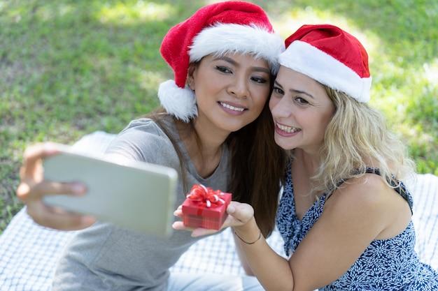 Lächelnde frauen, die selfie foto mit weihnachtsgeschenk im park machen