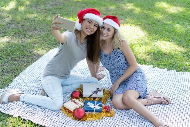 Lächelnde frauen, die selfie foto mit weihnachtsgeschenken auf gras machen