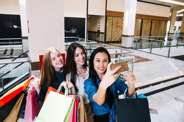 Lächelnde frauen, die selfie in der mall nehmen