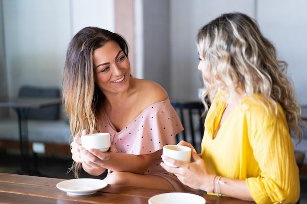 Lächelnde frauen, die spaß haben und kaffee im café trinken