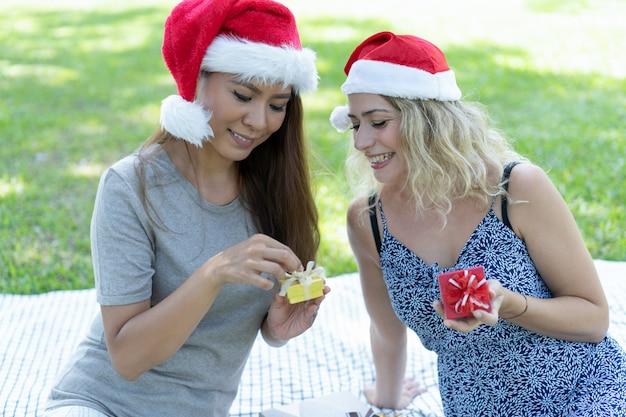 Lächelnde frauen, die weihnachtsgeschenke im park auspacken