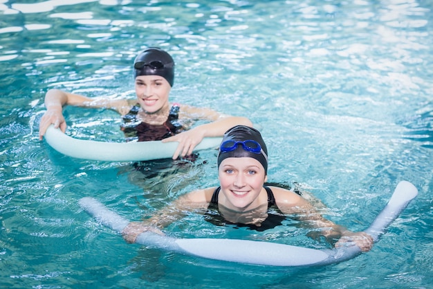 Lächelnde frauen im pool mit schaumstoffrollen im freizeitzentrum