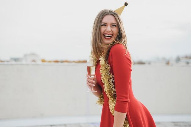 Lächelnde frauen im roten kleid, das ein champagnerglas hält