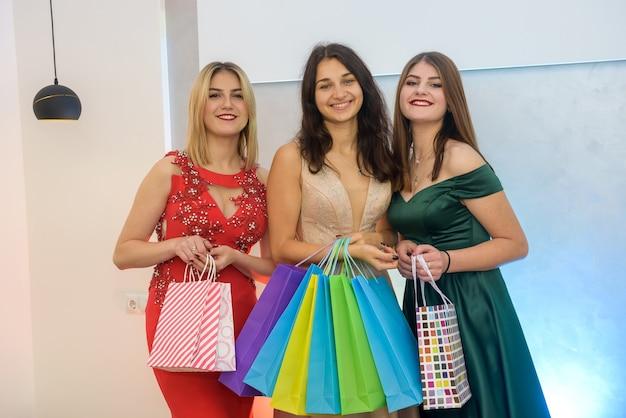 Lächelnde frauen in eleganten kleidern posieren mit geschenktüten im studio. weihnachtsgeschenke