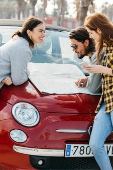 Lächelnde frauen mit smartphone nahe dem mann, der karte auf autohaube betrachtet